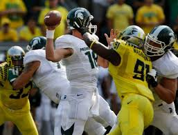 Michigan State quarterback gets a hard rush from Oregon linebacker Tony Washington.  Spartan loss to Oregon has apparently eliminated the Big 10 from playoff consideration.